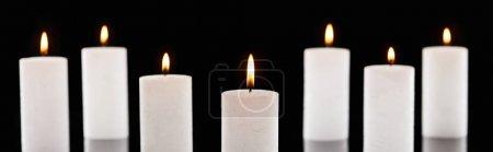 Foto de Enfoque selectivo de la quema de velas blancas que brillan aisladas en blanco y negro, disparo panorámico. - Imagen libre de derechos