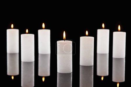 Photo pour Foyer sélectif de brûler des bougies blanches luisant isolé sur noir - image libre de droit
