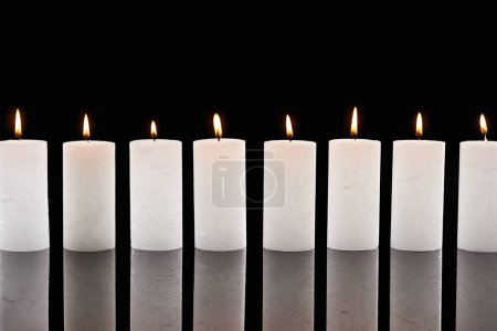 Photo for Burning white candles glowing in line isolated on black - Royalty Free Image