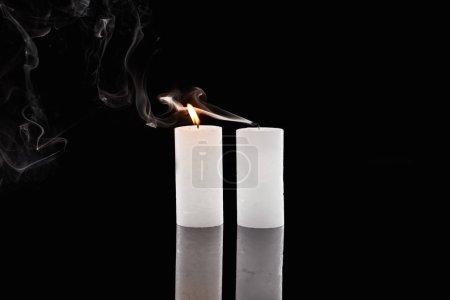 Photo for Burning and extinct white candles with smoke on black background - Royalty Free Image