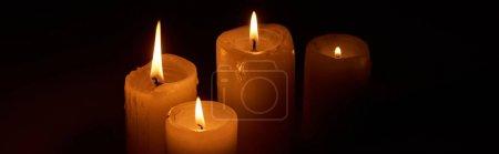 Photo pour Allumage de bougies dans l'obscurité sur fond noir, prise de vue panoramique - image libre de droit
