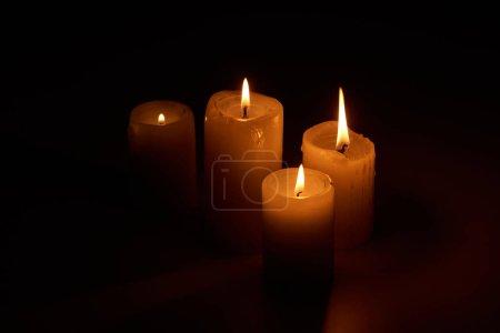 Photo pour Bougies allumées luisant dans l'obscurité sur fond noir - image libre de droit