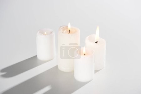Photo for Burning candles glowing on white background with shadow - Royalty Free Image