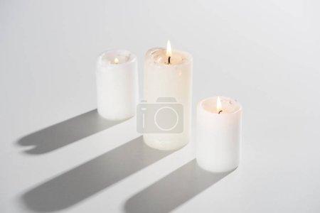 Photo pour Bougies allumées sur fond blanc avec ombre - image libre de droit