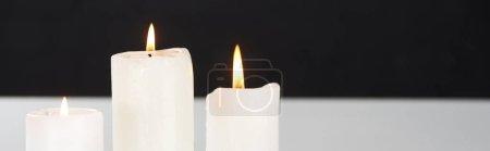Photo pour Brûlant des bougies blanches sur la surface blanche luisant isolé sur noir, plan panoramique - image libre de droit