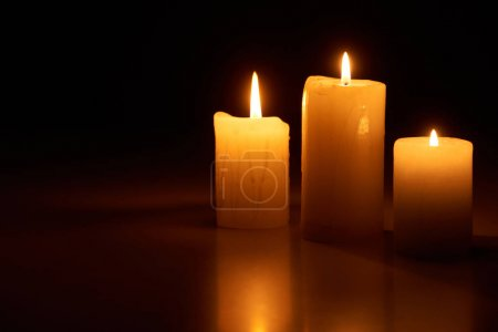 Photo pour Allumage de bougies lumineuses dans l'obscurité isolé sur noir - image libre de droit