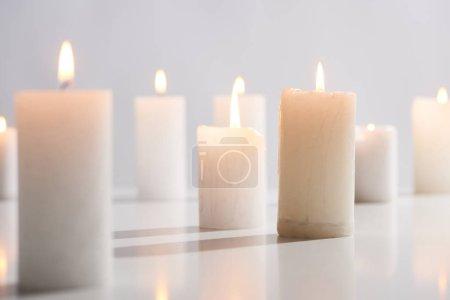 Photo pour Foyer sélectif de brûler des bougies blanches sur la surface blanche luisant isolé sur le gris - image libre de droit