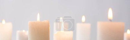 Photo pour Foyer sélectif de brûler des bougies blanches luisant isolé sur gris, panoramique coup - image libre de droit