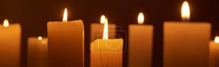Photo pour Foyer sélectif de brûler des bougies luisant dans l'obscurité, plan panoramique - image libre de droit