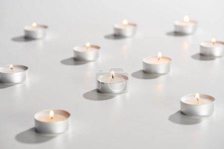 Photo pour Foyer sélectif des bougies allumées qui brillent sur la surface blanche - image libre de droit