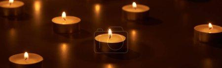 Photo pour Foyer sélectif de la combustion de bougies blanches luisant dans l'obscurité, plan panoramique - image libre de droit