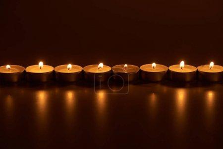 Photo pour Bougies blanches allumées dans l'obscurité - image libre de droit