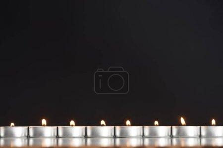 Foto de Velas encendidas dispuestas en línea resplandeciente aislado sobre negro - Imagen libre de derechos