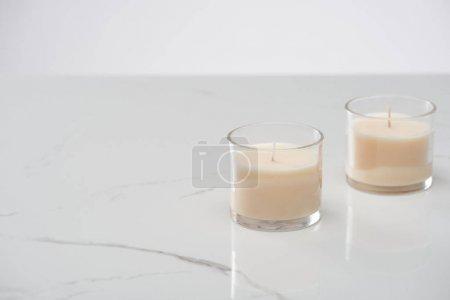 Photo pour Bougies blanches en verre sur marbre surface blanche - image libre de droit