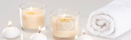 Photo for Burning white candles in glass and rolled towel on marble white surface, panoramic shot - Royalty Free Image