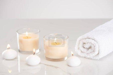 Photo pour Bougies blanches brûlantes en verre et serviette roulée sur marbre surface blanche - image libre de droit