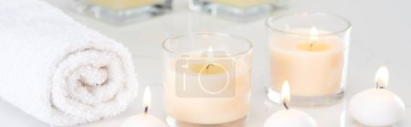 burning white candles in glass and rolled towel on marble white surface, panoramic shot
