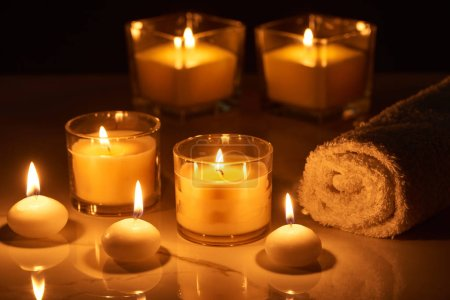 Photo for Selective focus of burning candles in glass glowing in dark near rolled towel on marble surface - Royalty Free Image
