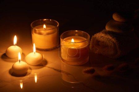 Photo pour Bougies allumées en verre brillant dans l'obscurité près de serviette roulée sur la surface du marbre - image libre de droit