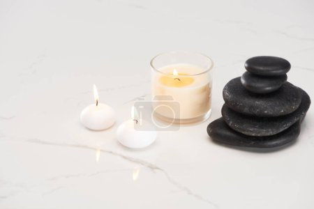 burning white candles in glass near spa stones and rolled towel on marble white surface