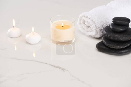 velas blancas ardientes en vidrio cerca de piedras de spa y toalla enrollada en la superficie blanca de mármol