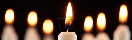 Photo pour Foyer sélectif de la combustion bougie blanche luisant isolé sur noir, tir panoramique - image libre de droit