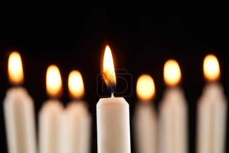 selective focus of burning white candle glowing isolated on black