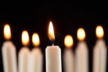 Foto de Enfoque selectivo de la quema de velas blancas que brillan aisladas en negro - Imagen libre de derechos