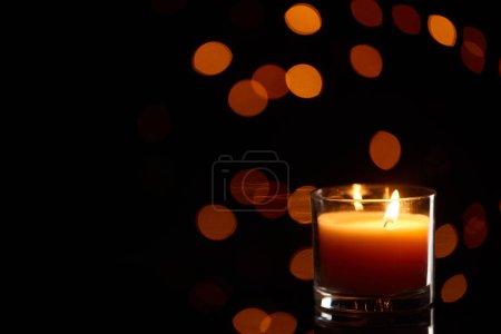 Photo pour Brûler une bougie luisant à l'obscurité avec des lumières bokeh en arrière-plan - image libre de droit