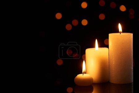 Photo pour Allumer des bougies luisant à l'obscurité avec des lumières de boucle sur le fond - image libre de droit