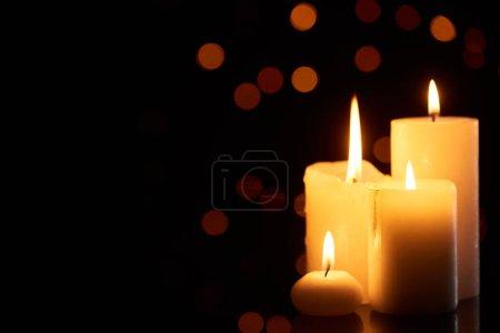 Photo pour Allumant des bougies luisant dans l'obscurité avec des lumières bokeh sur le fond - image libre de droit