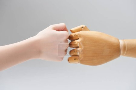 Photo for Cropped view of hands of woman and wooden doll making fist bump isolated on grey - Royalty Free Image