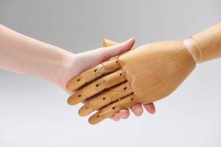 Photo for Cropped view of woman and wooden doll shaking hands isolated on grey - Royalty Free Image