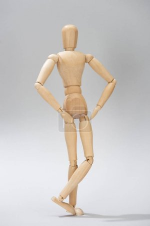Wooden doll with hands on hips on grey background