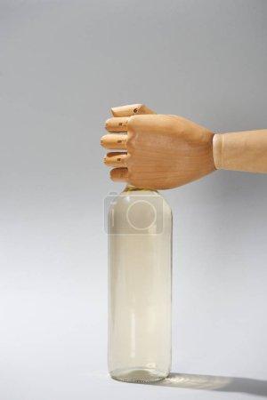Photo pour Main en bois de mannequin avec bouteille de vin sur fond gris - image libre de droit