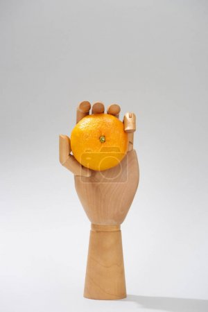 Photo for Wooden hand of doll with fresh mandarin on grey background - Royalty Free Image