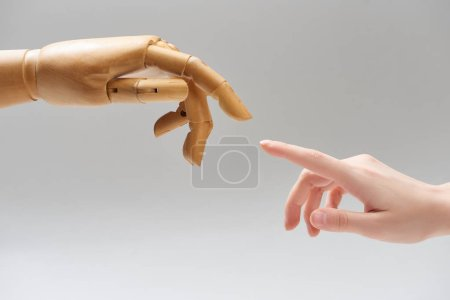Photo for Cropped view of woman and hand of wooden doll pulling fingers to each other isolated on grey - Royalty Free Image