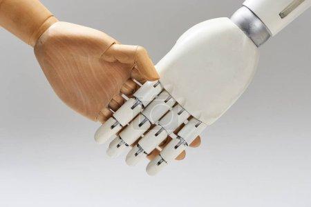 Photo pour Robot et poupée de bois serrant les mains isolé sur gris - image libre de droit