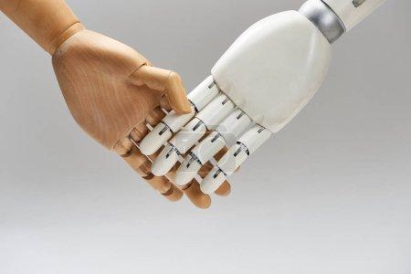 Photo pour Poupée de bois et poignée de main de robot isolées sur gris - image libre de droit