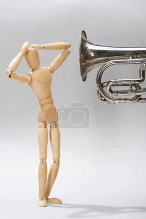 Wooden puppet with hands by head and alto horn on grey background