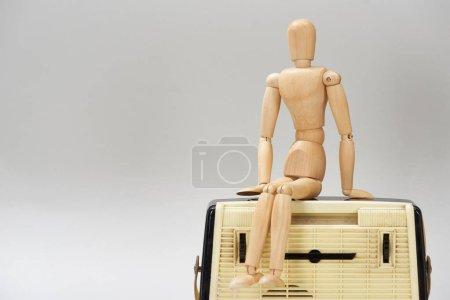 Photo pour Poupée en bois sur radio vintage isolée sur gris - image libre de droit