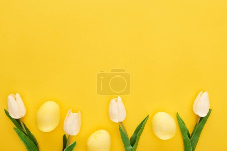 top view of tulips and painted Easter eggs on colorful yellow background