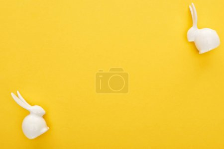 Photo for Top view of white Easter bunnies on colorful yellow background - Royalty Free Image