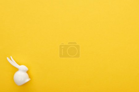 Photo for Top view of white Easter bunny on colorful yellow background with copy space - Royalty Free Image