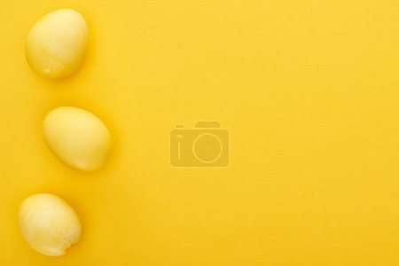 Photo for Top view of painted Easter eggs on colorful yellow background - Royalty Free Image