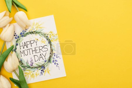 Photo pour Top view of spring tulips and happy mothers day greeting card on colorful yellow background - image libre de droit