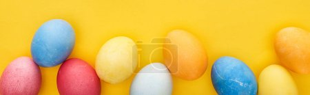 Photo for Top view of multicolored painted Easter eggs on yellow background, panoramic shot - Royalty Free Image