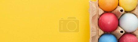 Photo pour Vue de dessus des oeufs de Pâques peints multicolores dans un récipient en carton sur fond jaune avec espace de copie, vue panoramique - image libre de droit