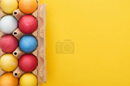Photo for Top view of multicolored painted Easter eggs in cardboard container on yellow background with copy space - Royalty Free Image