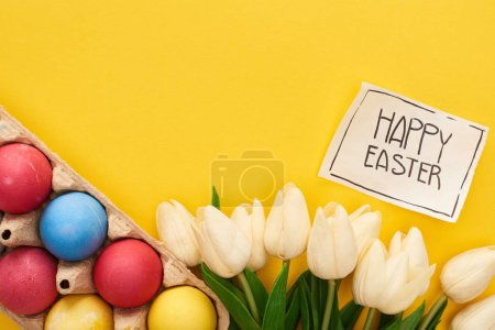 Photo pour Top view of painted eggs, tulips and greeting card with happy Easter lettering on yellow colorful background - image libre de droit